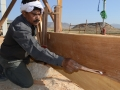 13 Babu, the Head Carpenter, shapes the garboard by marking the lower edge with the qalam